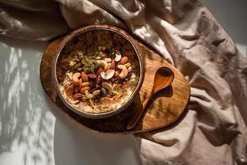 Oatmeal porridge in coconut bowl with wooden spoon on natural wooden tray. Porridge oats with almonds, pistachios and other nuts. Shadow of sunrise morning. White background. Top view or flat lay.