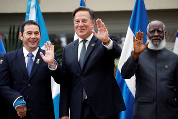 Guatemala's President Jimmy Morales, Panama's President Juan Carlos Varela and Belize's Foreign Minister Wilfred Elrington wave during a family photo of the Central American Integration System in Guatemala City