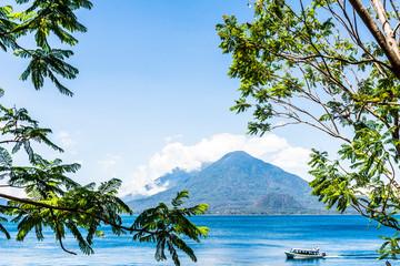 Passenger boat or public water taxi cruises on lake with Toliman & Atitlan volcanoes behind at Lake Atitlan, Guatemala