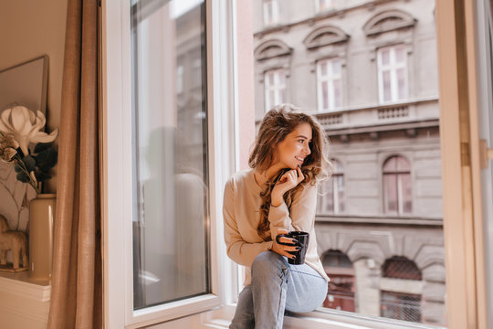 Romantic female model in good mood looking at street, sitting on sill. Fascinating dark-haired lady spending morning at home, chilling near window with coffee.