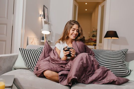 Cheerful girl sitting on couch with blanket and cushions and smiling. Spectacular brunette lady laughing, while drinking coffee under plaid.