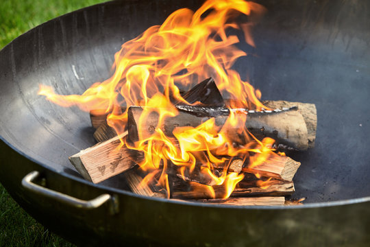 Logs on fire covered in burn marks during cookout