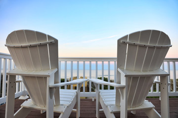 relax on Adirondack chairs in a desk balcony overlooking the beach and  ocean at sunset.  Add a beverage to this travel image.