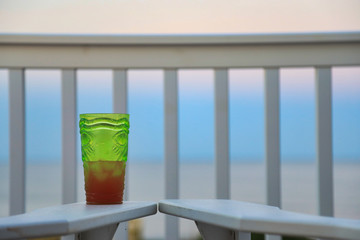 Enjoy a beverage while looking out over the beach and ocean at sunset. in this tropical travel vacation image.