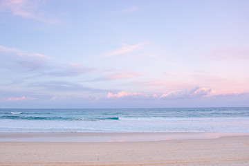 pretty pastel colour sky pink purple blue with fluffy cloud on beach with white sand Australia Gold Coast