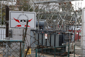 """A placard that reads: """"Danger of death, high tension"""", is seen in a power plant in a neighborhood at Valparaiso"""
