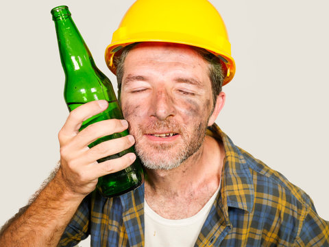 thirsty and tired constructor worker or builder man in safety helmet feeling exhausted holding cold beer bottle against his face refreshing during work break isolated