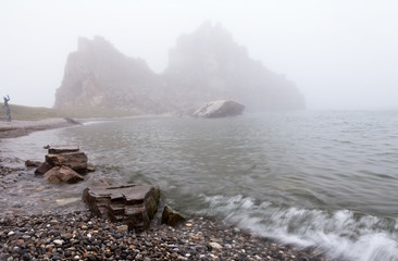Lake Baikal. Olkhon Island in the August Rains. Silhouette of the famous Shamanka Rock and a pebble beach in the fog. Unusual summer landscape