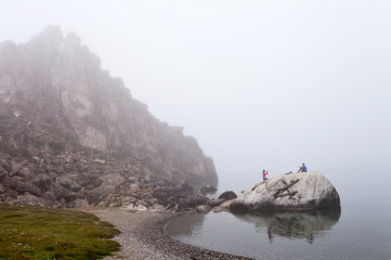 Baikal Lake in summer. Olkhon Island in rainy and foggy weather. Tourists are photographed on a stone near the Shamanka Rock. Summer unusual landscape