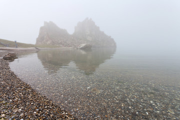 Baikal Lake. Olkhon Island in rainy and foggy weather. Pebble beach and Shamanka Rock  hiding in the fog. Summer unusual landscape. A natural phenomenon