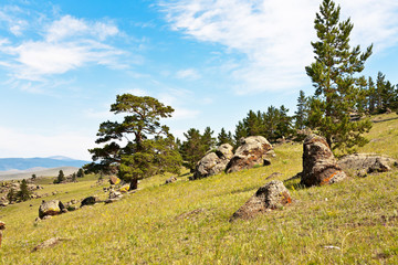 Baikal region. Tazheranskaya steppe with beautiful weathering stones on green hills. Natural Park. Tourist routes along the shore of Lake Baikal. Summer landscape