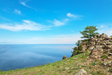 Lake Baikal in summer sunny day. June fogs on blue water near the coast of Olkhon Island. Natural background, lakeside landscape