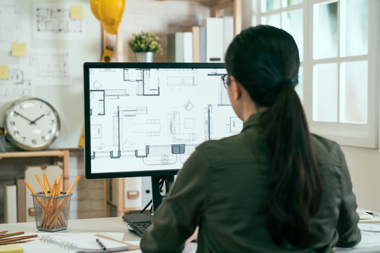Back view portrait of asian woman engineer working on desktop computer with blueprints on screen in office. young female architect worker sitting in studio looking at pc screen interior design plan