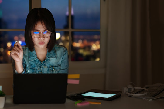 Candid of young attractive asian female student sitting on desk with smart digital gadget looking at notebook working at late night with project research, graphic designer or programmer concept.