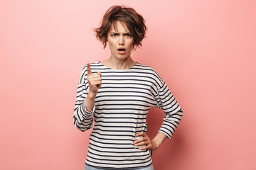 Wall Mural - Displeased beautiful woman posing isolated over pink wall background make stop gesture.