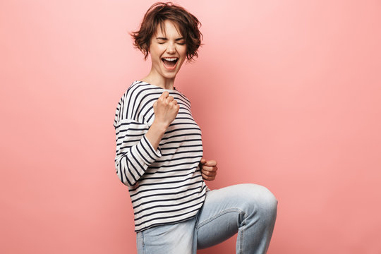Woman posing isolated over pink wall background make winner gesture.