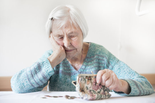 Concerned elderly 96 years old woman sitting at table at home and counting remaining coins from pension in her wallet after paying bills. Unsustainability of social transfers and pension system.