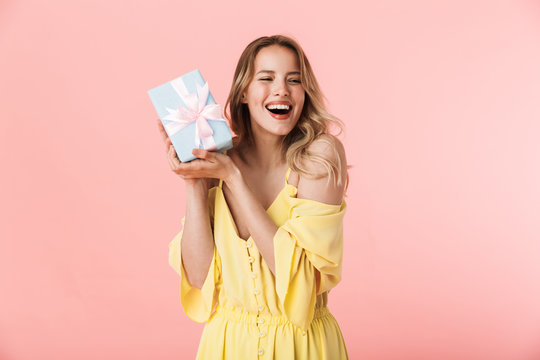 Happy young blonde woman posing isolated over pink wall background holding present gift box.