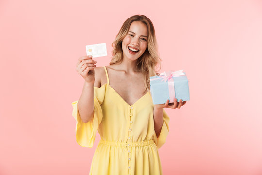 Excited emotional happy young blonde woman posing isolated over pink wall background holding present gift box and credit card.