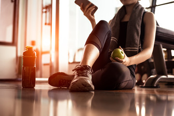 Close up of woman using smart phone and holding apple while workout in fitness gym. Sport and Technology concept. Lifestyles and Healthcare theme.