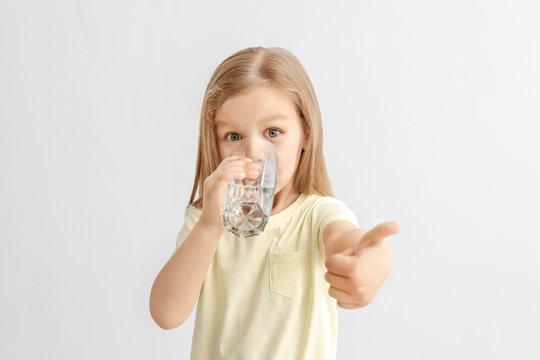 Cute little girl drinking water on light background