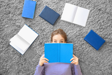 Young woman with books lying on carpet