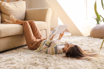 Beautiful young woman reading book while lying on floor at home