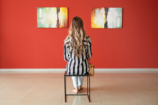 Woman sitting on chair in modern art gallery
