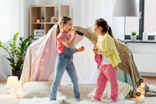 childhood, hygge and friendship concept - happy girls with guitar and microphone playing music and singing near kids tent or teepee at home