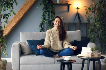 Cute smiling woman is learing yoga at home