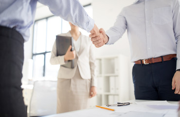 business, cooperation and partnership concept - close up of businessmen or architects making handshake at office
