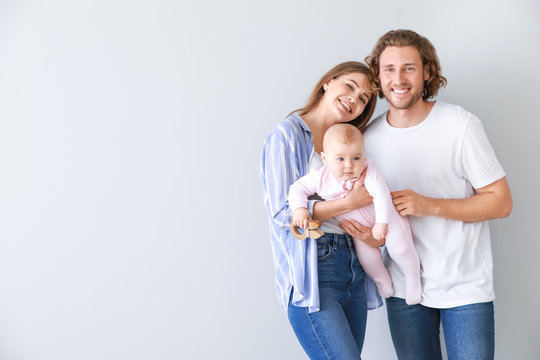 Happy parents with cute little baby on light background