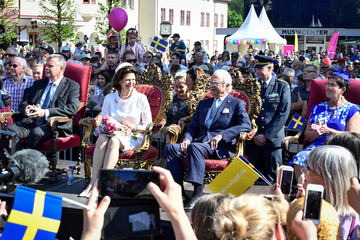 Sweden's Queen Silvia and King Carl XVI Gustaf  together with  the Governor of Dalarna Ylva Thorn and her husband Lasse Thorn  sit on chairs at the town square in Borlange