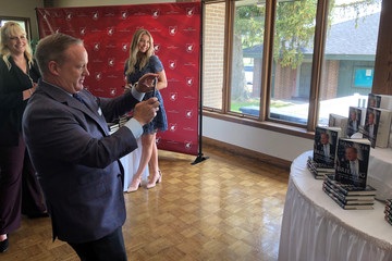 Former White House spokesman Sean Spicer takes a picture of his own book display at a Republican lunch in Marion, Ohio