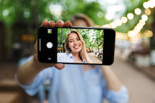 Excited happy young woman posing outdoors in park take a selfie by mobile phone.