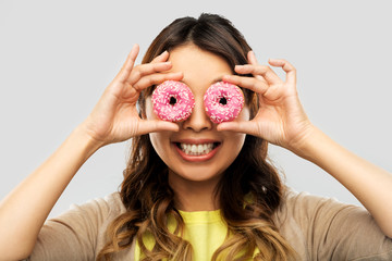 people, fast food and fun concept - happy asian young woman with donuts instead of eyes over grey background