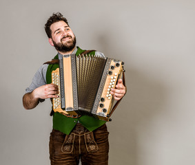 cool young musician with black beard and leather trousers and traditional costume and accordion is posing in front of grey background