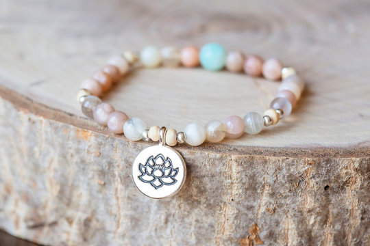 Mineral stone sun stone and lotus pendant bead bracelet on natural wooden background