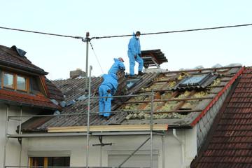 Dachdecker decken Dach mit Asbestfaserzementplatten ab