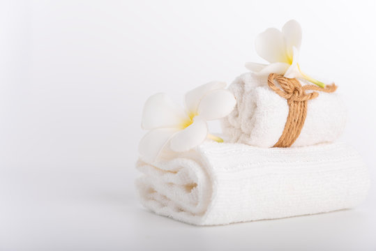 White rolled towels decorate with Frangipani flowers spa object on white background