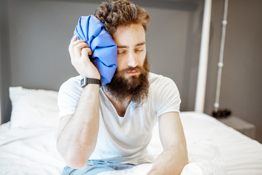 Man feeling bad, sitting on the bed with headache and applying ice bag