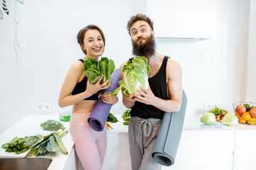 Portrait of a young couple in sportswear standing together with yoga mats and healthy fresh food on the kitchen at home