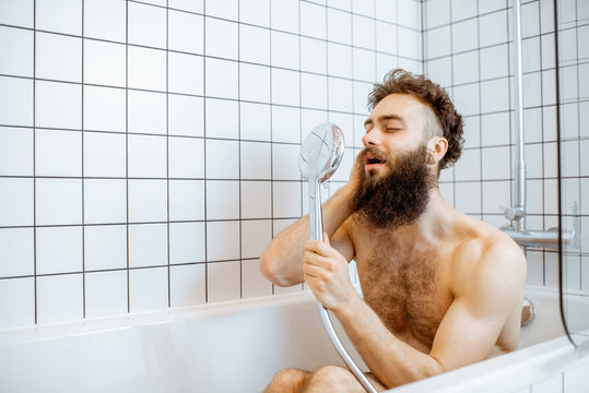 Joyful bearded man washing in the bathtub, having fun singing into the shower in the bathroom