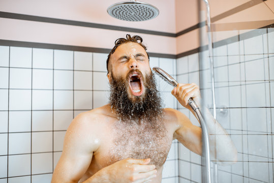 Bearded man feeling shocked while taking a shower with cold water in the bathroom at home