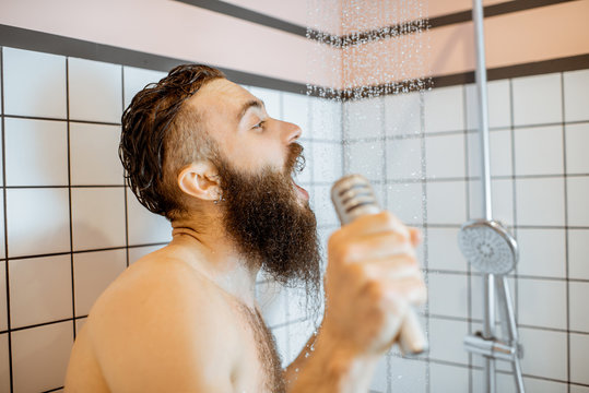Joyful bearded man singing into the micrphone while taking a shower in the bathroom