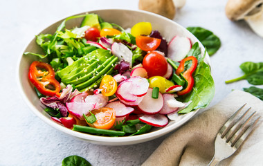 Fresh vegetable salad bowl closeup, healthy organic vegetables salad with radish, spinach, tomatoes, onion, avocado