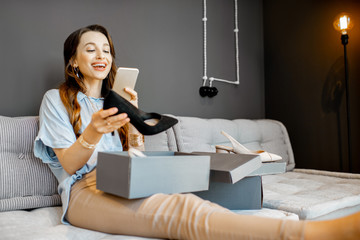 Young woman feeling excited with a new shoes, unpacking purchases and taking photo with phone at home