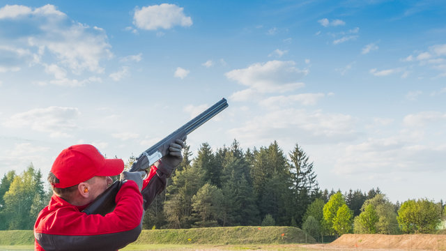 trap or skeet shooting, man in red clothes  shoots from a shotgun at clay pigeon,  a background of forest and sky