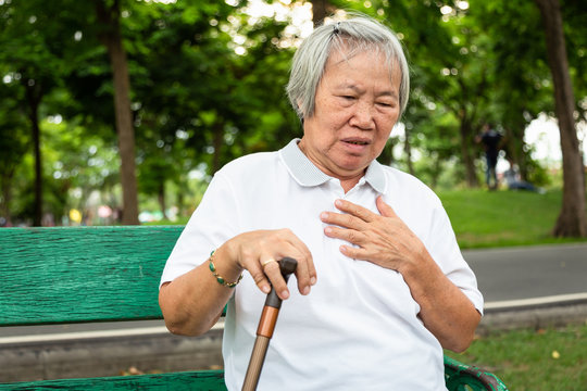 Asian elderly with certain symptoms,difficulty breathing, heart problems,Communicates the symptoms of heart disease,senior woman with chest pain suffering from heart attack in park,healthcare concept