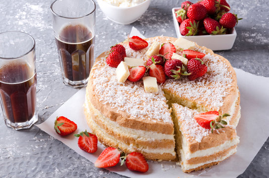 Piece of sponge cake, strawberries, glasses of hot coffee on the grey surface.Setting table for eating little snack